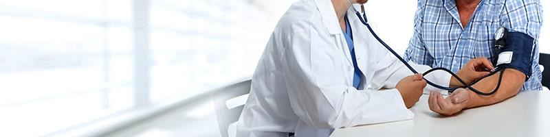 doctor checking mans blood pressure